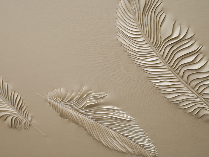 Detail of hand-sculpted artwork by Helen Amy Murray with feathers in cream faux leather