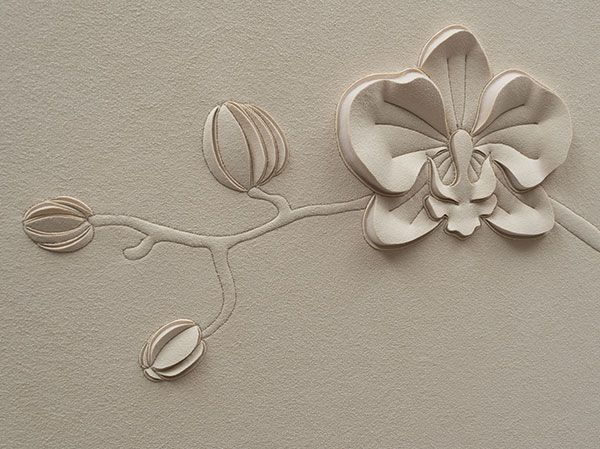 Close up detail of a hand-sculpted orchid flower and buds in off-white faux suede