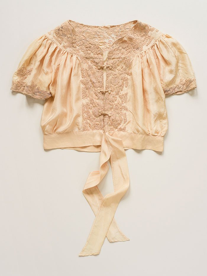 Photograph of an antique peach silk blouse, with delicate embroidered lace detail on white background